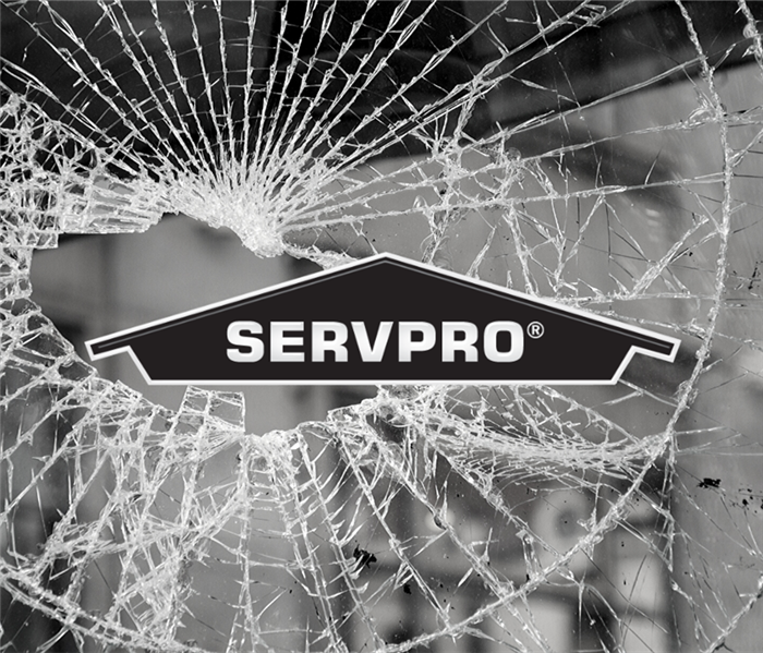 Broken glass window with black SERVPRO logo on top