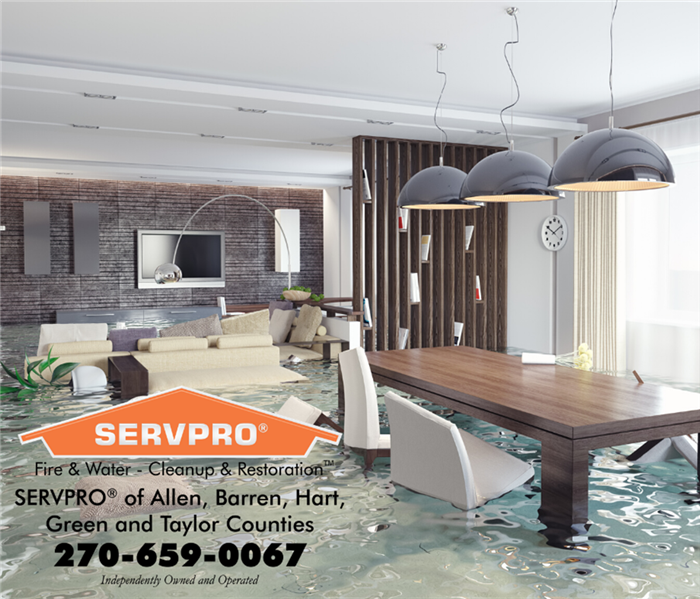 Photo of a flooded living room and dinning room in a beautiful house. SERVPRO logo in lower left corner.