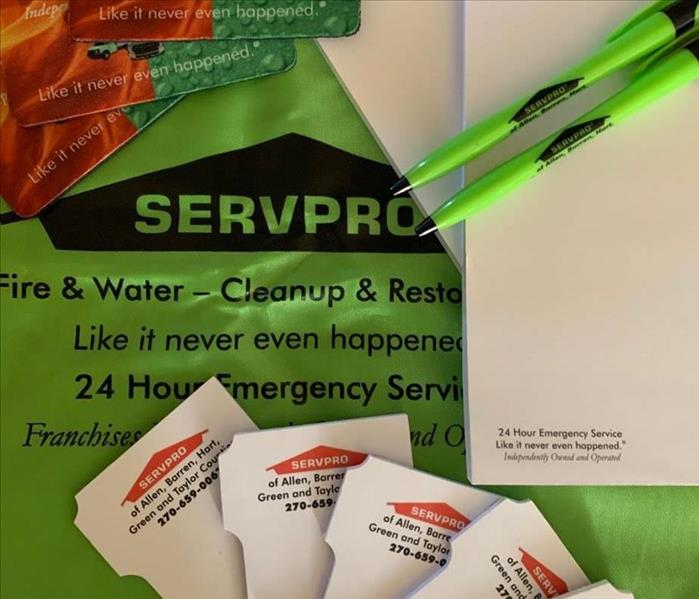 SERVPRO background with pens, note pads and coasters laid around with SERVPRO logos and phone numbers on each item